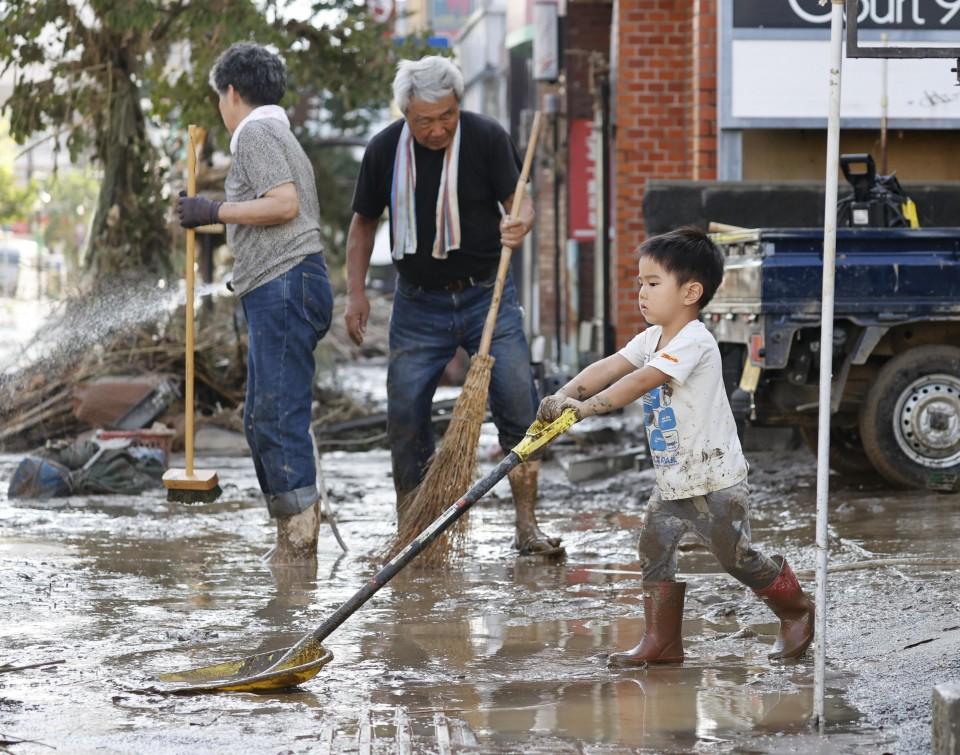 طفل يساعد في أعمال التنظيف بعد الفيضان في هيتويوشي، كوماموتو | عبر وكالة كيودو